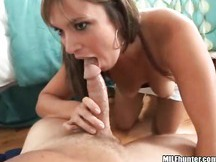 A hot busty milf named April sits down and starts to suck on some cock